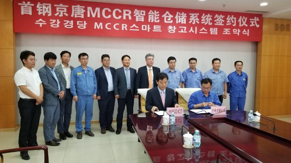 Kim Kwang-seok (left, front row), president of POSCO ICT China, and Qiu Yinfu, president of Shougang Jingtang United Iron & Steel Co., sign an unmanned crane system contract on June 27.