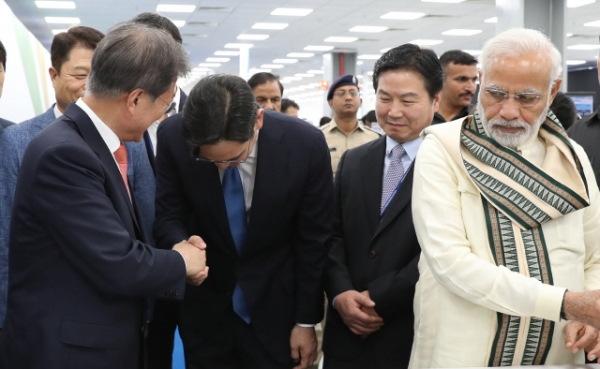 Prime Minister Narendra Modi casts a sidelong glance at Samsung Electronics Vice Chairman Lee Jae-yong bowing deeply at the waist when President Moon Jae-in extends his hands for a handshake at a Samsung Electronics' smartphone factory completion ceremony in Noida, on July 9, 2018 (local time).