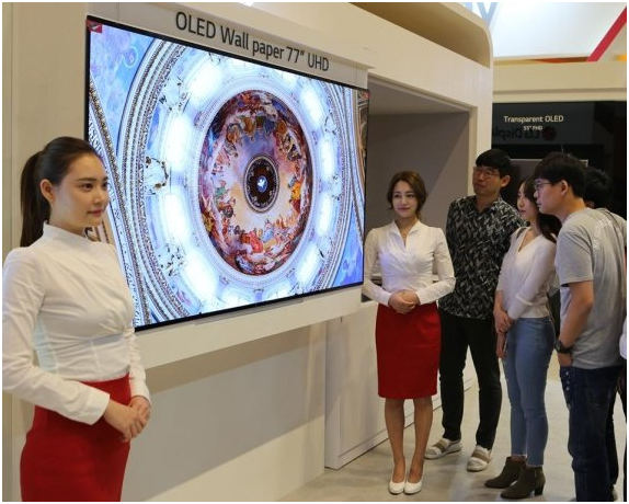 Visitors are taking a look at LG Display's 77-inch wallpaper OLED product.