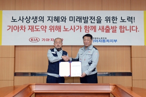 Kang Sang-ho, a representative of the Korean Metal Workers' Union Kia Motors branch, left, and Kia Motors vice president Choi Jun-young, pose for a photo after signing a final agreement on ordinary wages.