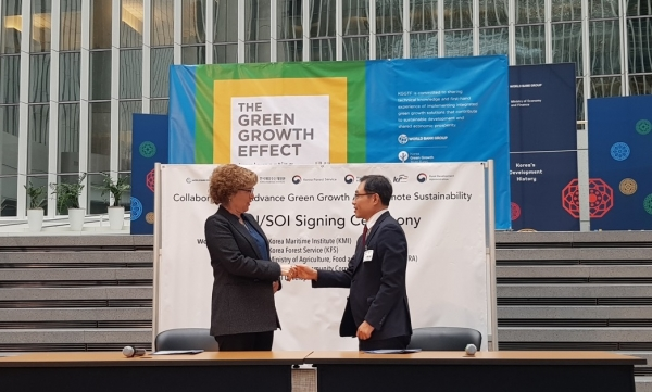 Choi Byung-am (right), deputy director of the Korea Forest Service, shakes hands with Karin Kemper, global director of World Bank.